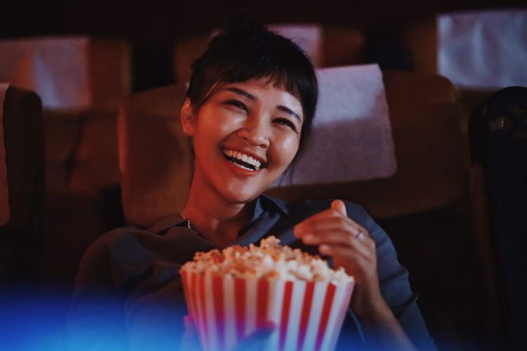 Portrait of smiling woman having popcorn at theater