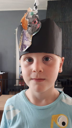Close-up portrait of cute boy wearing paper crown at home