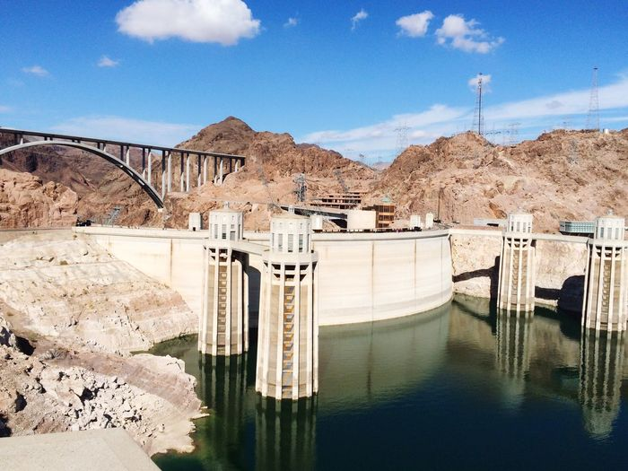 Hoover dam by rocky mountains against sky