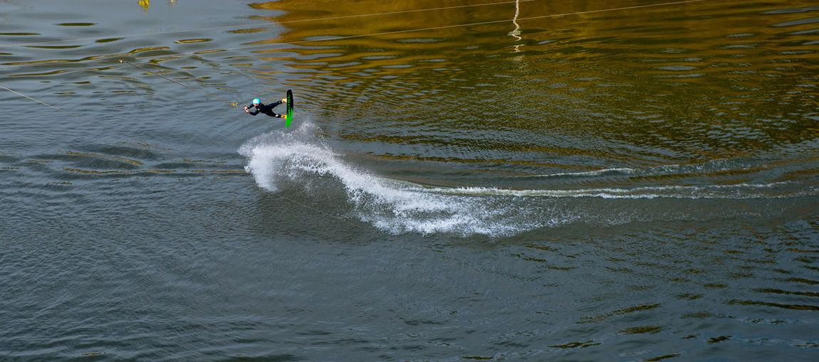 Man wakeboarding over lake