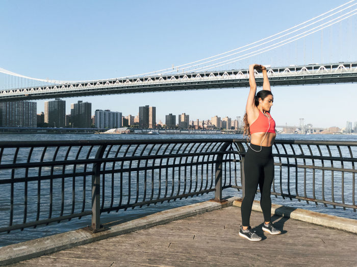 Young athletic woman stretches along the water in New York City Architecture Built Structure Full Length Standing City Connection Railing Bridge Sky Day One Person Lifestyles Young Adult Bridge - Man Made Structure Building Exterior Water Real People Young Women Nature Adult Outdoors