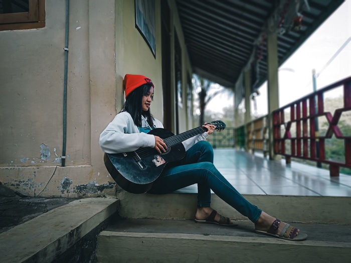 Side view of women playing guitar