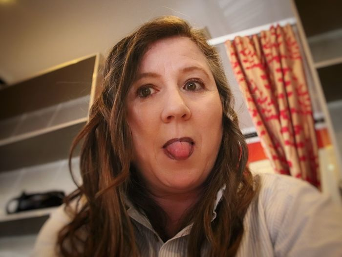 Low Angle Portrait Of Woman Sticking Out Tongue At Home