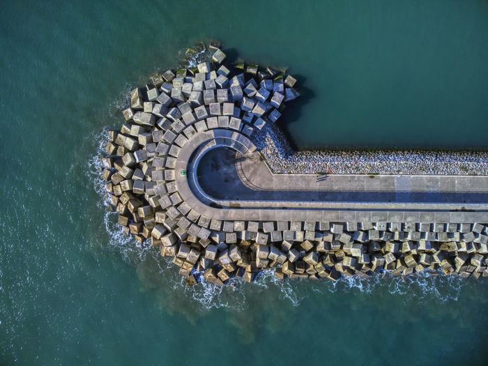 Aerial view of cement blocks protecting the shore from the waves in the port of luanco in asturias.