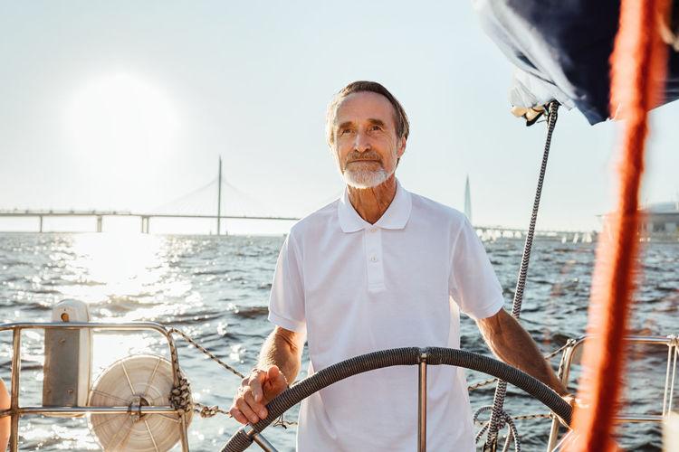 Senior man standing in sailboat against sky