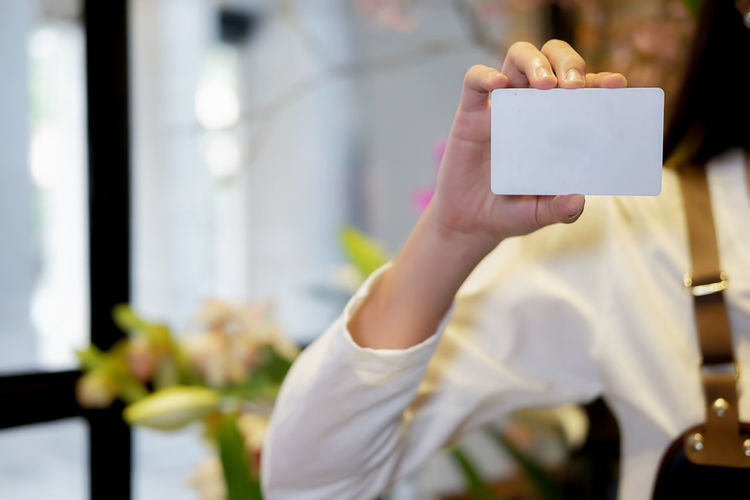 Midsection Of Woman Holding Blank Business Card