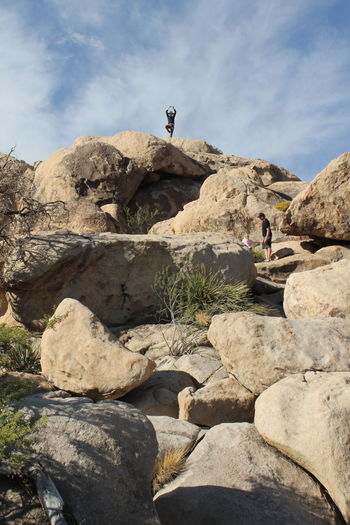 Low angle view of man doing tree pose on rocks