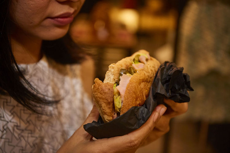 Sandwich in her hand One Person Holding Food And Drink Food Women Adult Unhealthy Eating Indoors  Fast Food Ready-to-eat Snack Sandwich Human Hand Hand Freshness Lifestyles Meal Young Adult Eating Bread Take Out Food Restaurant Hamburger Focus On Foreground Hot Dog