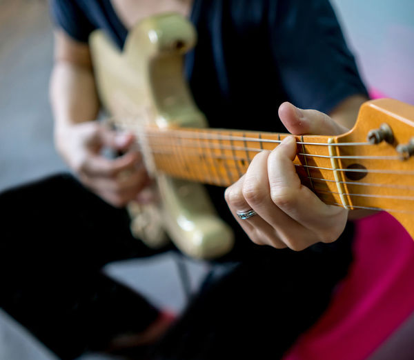 Close up of woman hand playing electric guitar. Maple neck and fingerboard. Selective focus. Retro Sound Acoustic Guitar Arts Culture And Entertainment Close-up Day Fretboard Guitar Holding Human Body Part Human Hand Indoors  Leisure Activity Lifestyles Men Midsection Music Musical Instrument Musical Instrument String Musician One Person Performance Play Playing Plucking An Instrument Real People Skill  Vintage