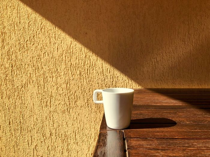 Minimalistic shot of a white cup sitting in the bright sunlight on a wooden table Simplicity No People Nobody Minimalist Minimal Minimalism Light And Shadow Shadow Reflection Sunrays Sunlight Sunny Sun Day Rustic Wooden Table Room Balcony Terrace Beverage Coffee White Cup Mug Coffee Cup Coffee - Drink Still Life Freshness Drink Wood - Material