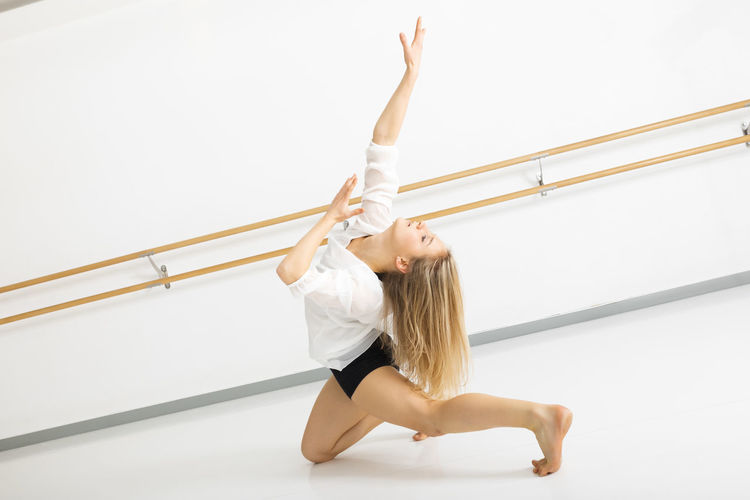 Young Woman With Exercising At Ballet Studio