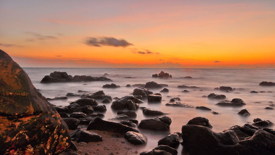 The reefs on the beach hit the sunset waves. Beach Beauty In Nature Cloud - Sky Clouded Horizon Over Water Nature No People Orange Color Outdoors Pervade Reef Rock - Object Scenics Sea Sky Sunset Tranquil Scene Tranquility Water Wave