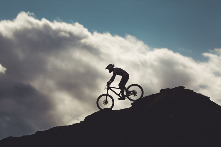 Low angle view of silhouette man riding bicycle against sky