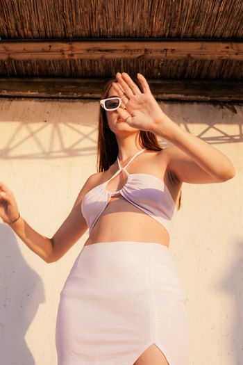 Midsection of woman with mobile phone standing outdoors