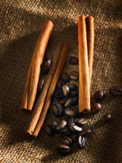 cinnamon sticks and coffee beans Coffee Brown Cinnamon Sticks Close-up Coffee Bean Day Food Food And Drink Food Stories Freshness High Angle View Indoors  No People Roasted Coffee Bean Sackcloth Spice Textured  Wood - Material