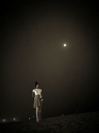 Full length of woman standing at beach against sky during night