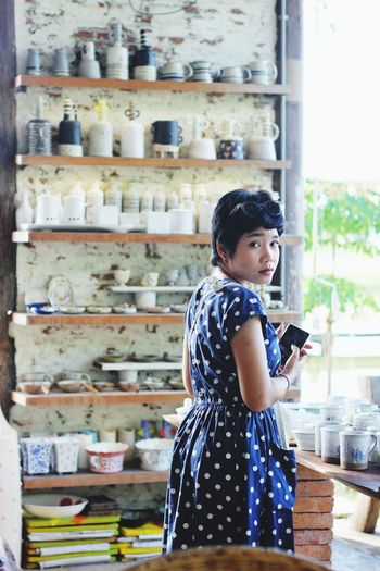 Portrait Of Young Woman Wearing Polka Dot Dress While Standing In Ceramics Market