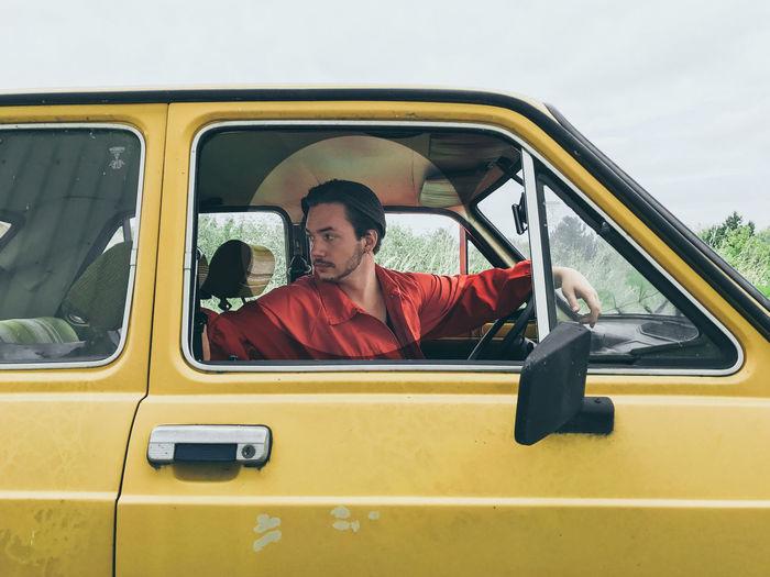Portrait of man sitting in car against sky