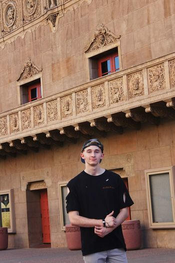 Portrait of young man standing against historic building