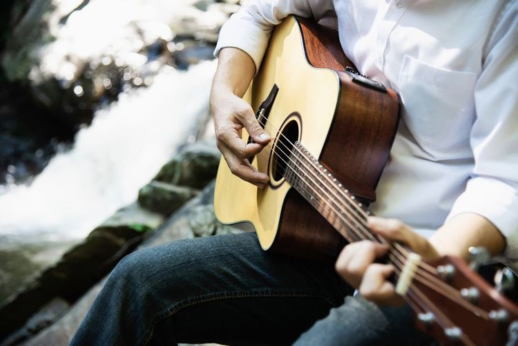 Midsection man playing guitar while sitting by river