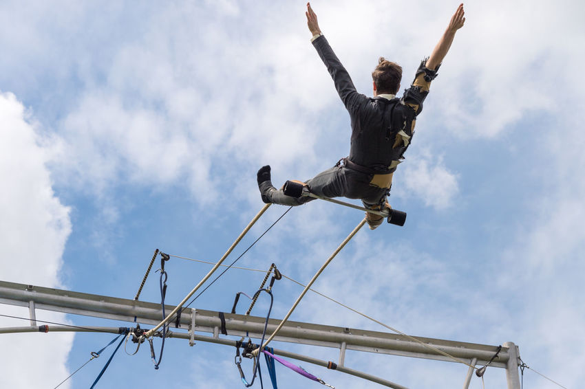 Montreal, Canada - 4 June 2017: Trapeze artist performing outside In Jeanne Mance Park Artist Breathtaking Circus Falling Man Acrobat Aerial Danger Fall Low Angle View One Person Outdoors Sky Trapeze Artist