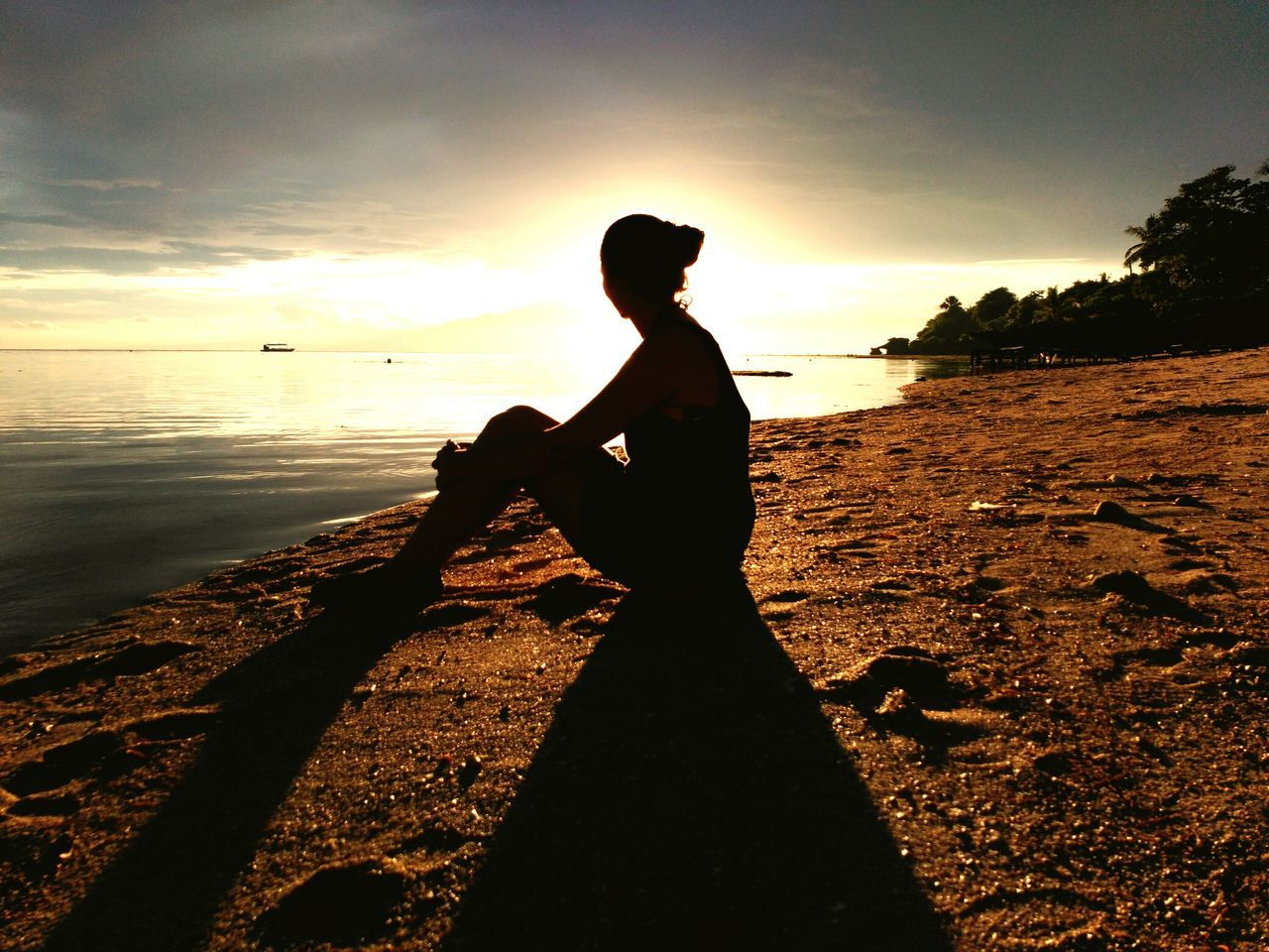 silhouette, one person, sunset, water, tranquil scene, beach, side view, sea, real people, tranquility, nature, sky, sitting, scenics, beauty in nature, outdoors, horizon over water, full length, leisure activity, standing, women, lifestyles, vacations, day, tree, young adult, people