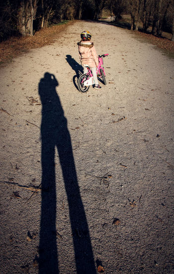 Adult Bicycle Child Childhood Day Full Length Girls High Angle View Lifestyles Looking Outdoors People Photographer Real People Riding Shadow Sunlight Togetherness Two People