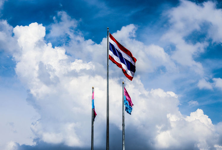 Low angle view of flags waving against cloudy sky