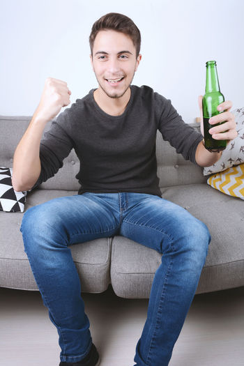 Young man watching sport tv with beer and celebrating. Indoors. Smiling One Person Looking At Camera Portrait Sitting Happiness Front View Casual Clothing Bottle Lifestyles Furniture Indoors  Young Men Young Adult Sofa Real People Container Leisure Activity Three Quarter Length