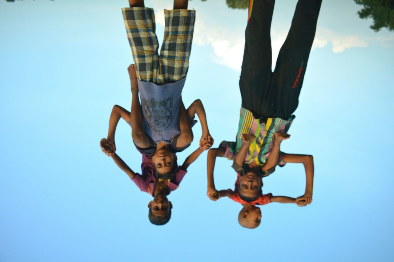 real people, togetherness, leisure activity, upside down, full length, day, friendship, lifestyles, boys, looking at camera, teamwork, low angle view, group of people, clear sky, men, blue, adventure, childhood, outdoors, sky, bonding