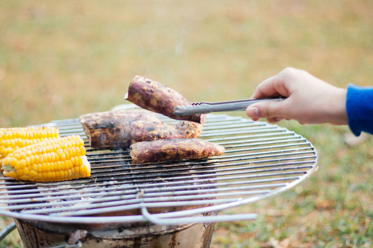 Cropped image of meat on barbecue grill