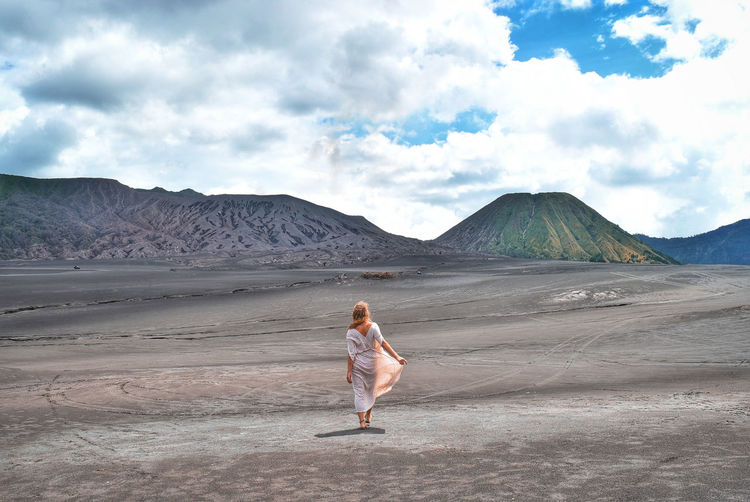 Rear View Of Woman Walking On Land Against Cloudy Sky