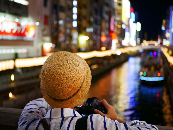 Rear view of woman photographing illuminated boat in city at night