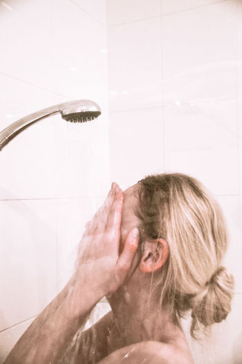 Side view of woman having shower in bathroom