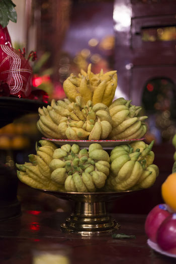 Vertical photo of Buddha's hand fruit offerings on platters in temple, Hanoi, Vietnam Freshness Fruit Indoors  Close-up Tropical Fruit Religion Focus On Foreground Buddha's Hand Fruit Offerings Platters Hà Nội, Việt Nam Temple Worship Buddhism Food No People Traditional Dim Light