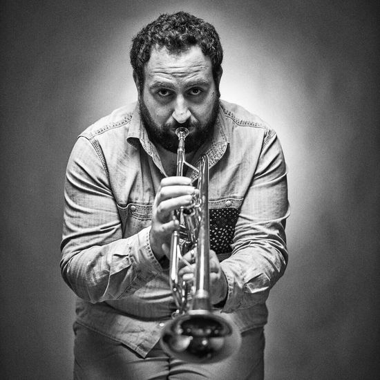 Portrait Of Man Playing Trumpet While Standing Against Gray Background