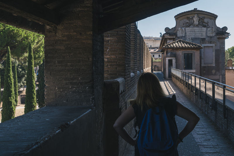 Rear view of woman standing by historic building