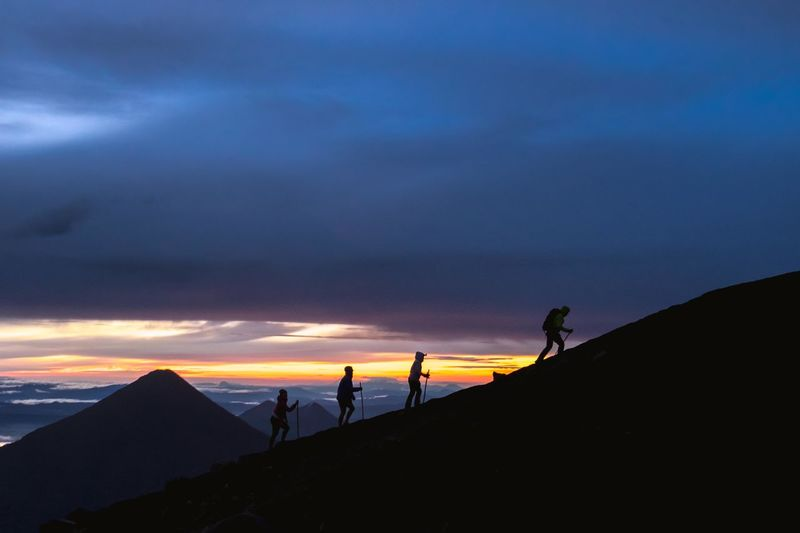 Silhouette People Hiking On Mountain Against Cloudy Sky During Sunset