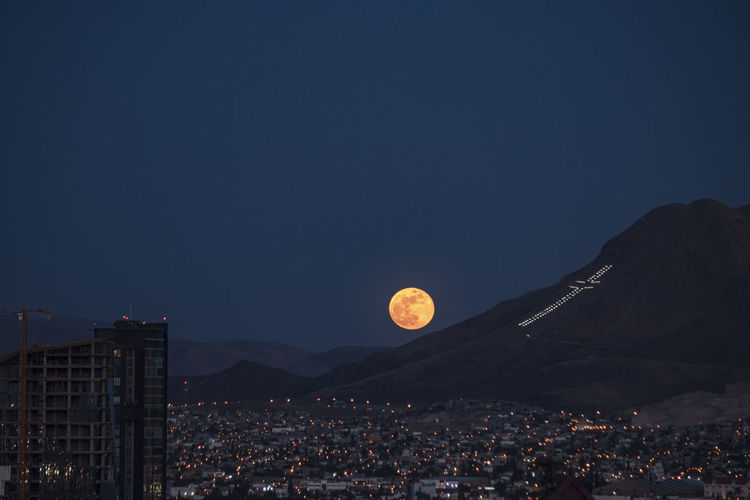 Aerial view of full moon over city against sky at dusk