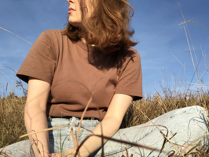 Midsection of woman sitting on field against sky