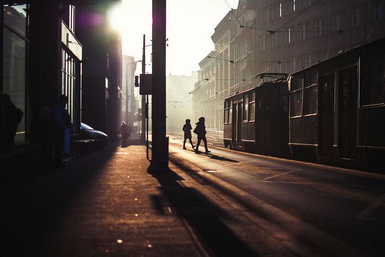 Silhouette people walking on road