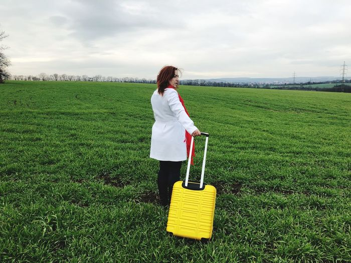Rear view woman holding luggage while standing on field