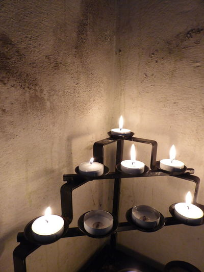 Close-up of lit tea light candles against wall