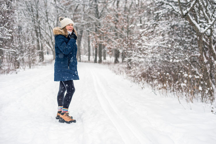Woman standing in snow covered tree