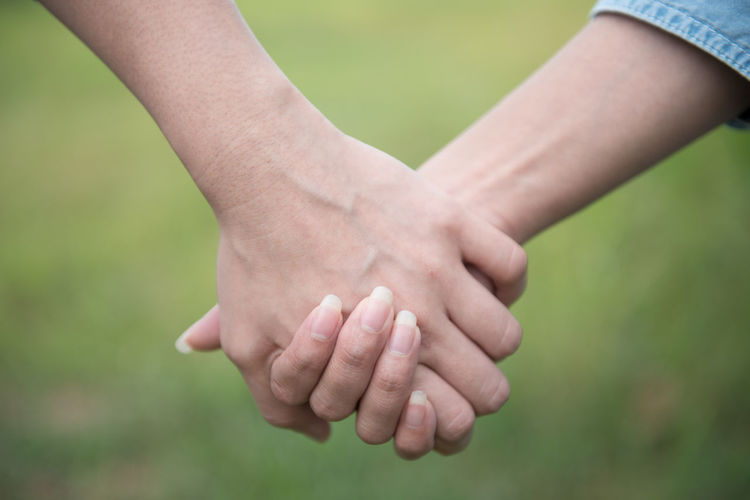 Two woman Lesbian couple holding their hands lesbian concept Human Hand Hand Human Body Part Real People Focus On Foreground Body Part Bonding Positive Emotion Finger Two People Togetherness People Human Finger Day Love Women Close-up Men Adult Green Color Outdoors Couple - Relationship Human Limb