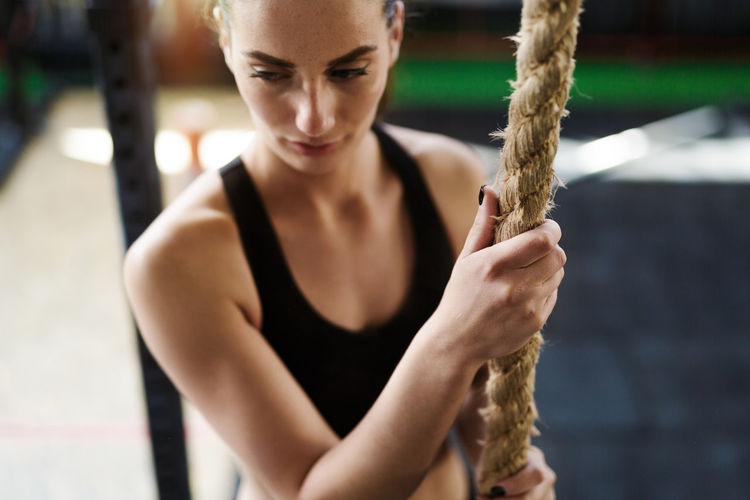 High angle view of young woman holding rope looking away while standing in gym
