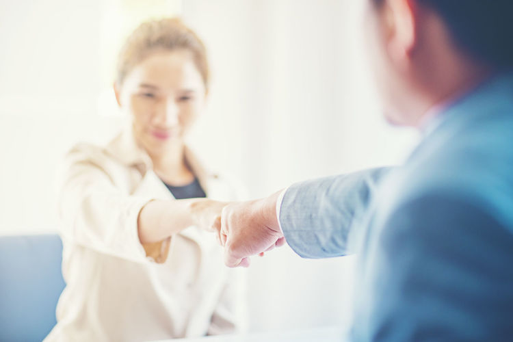 Business people doing fist bump while sitting in office