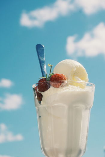 Close-up of ice cream in glass against sky