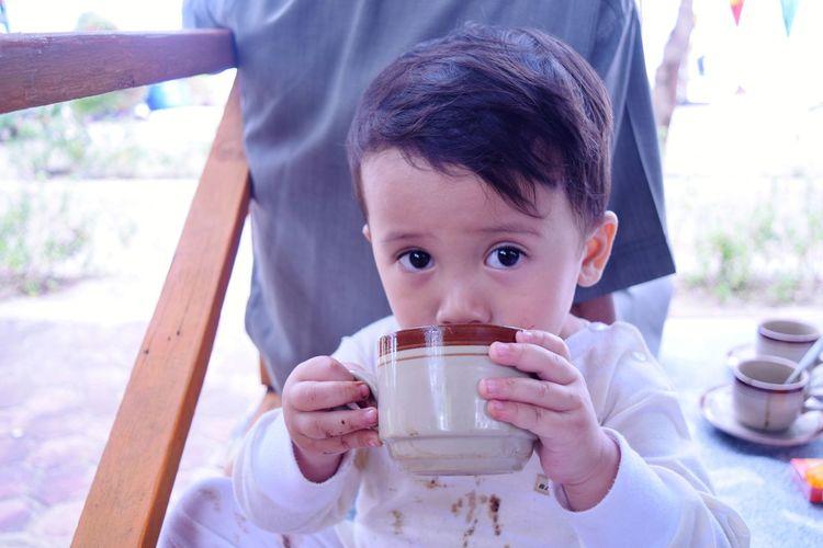 Portrait of boy drinking coffee