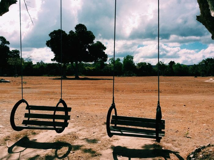 Swings hanging in ground against cloudy sky